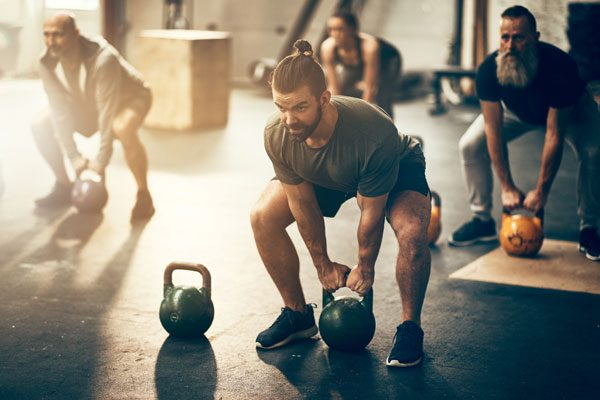 exercise class working out with kettlebells in gym